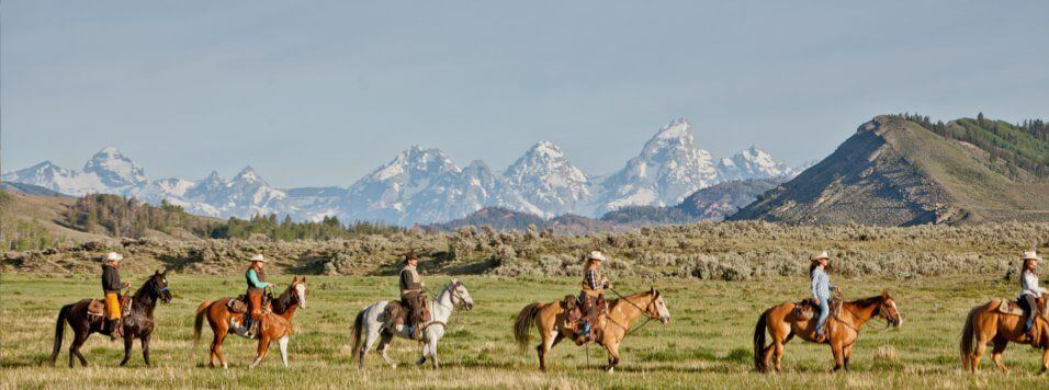 Horseback riding Jackson Hole with Grand Tetons in the background