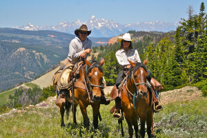 Jimmy and Tiffany riding their horses with the Tetons in the background