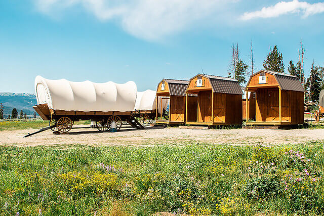 Jackson Hole glamping at Goosewing Ranch in covered wagons and private baths featuring hot water, showers, sink, and toilet.