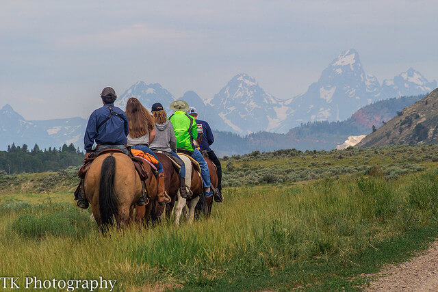 Jackson Hole glamping at Goosewing Ranch include daily opportunities for horseback trail rides with the majestic Grand Tetons in the distance.