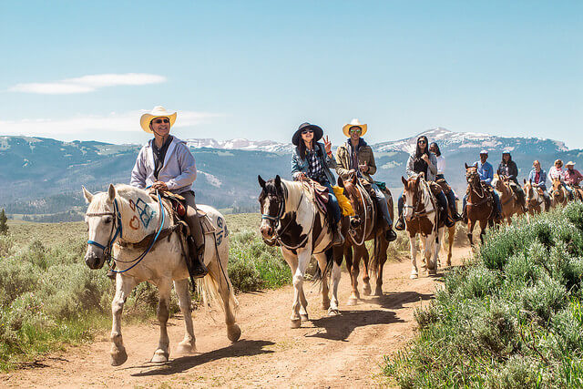 A dude ranch experience makes a great multigenerational vacation, including trail rides.